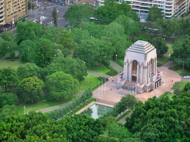 The ANZAC Memorial building and pool of reflection in the green parklands of Hyde Park.