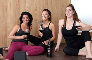Three women in activewear sitting around drinking wine