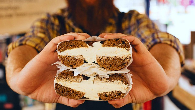 Man holding bagel with cream cheese