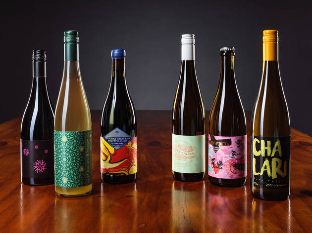 Six bottles of natural wine on a wooden table