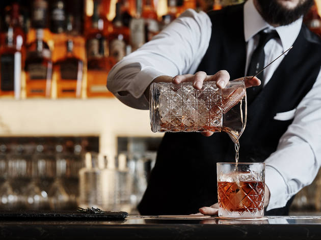 A bartender pouring a Negroni from mixing glass into a tumbler at Mullane's