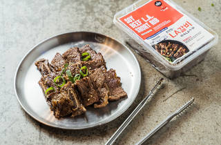 A metal plate of beef short ribs and their packaging alongside, with a pair of tongs.