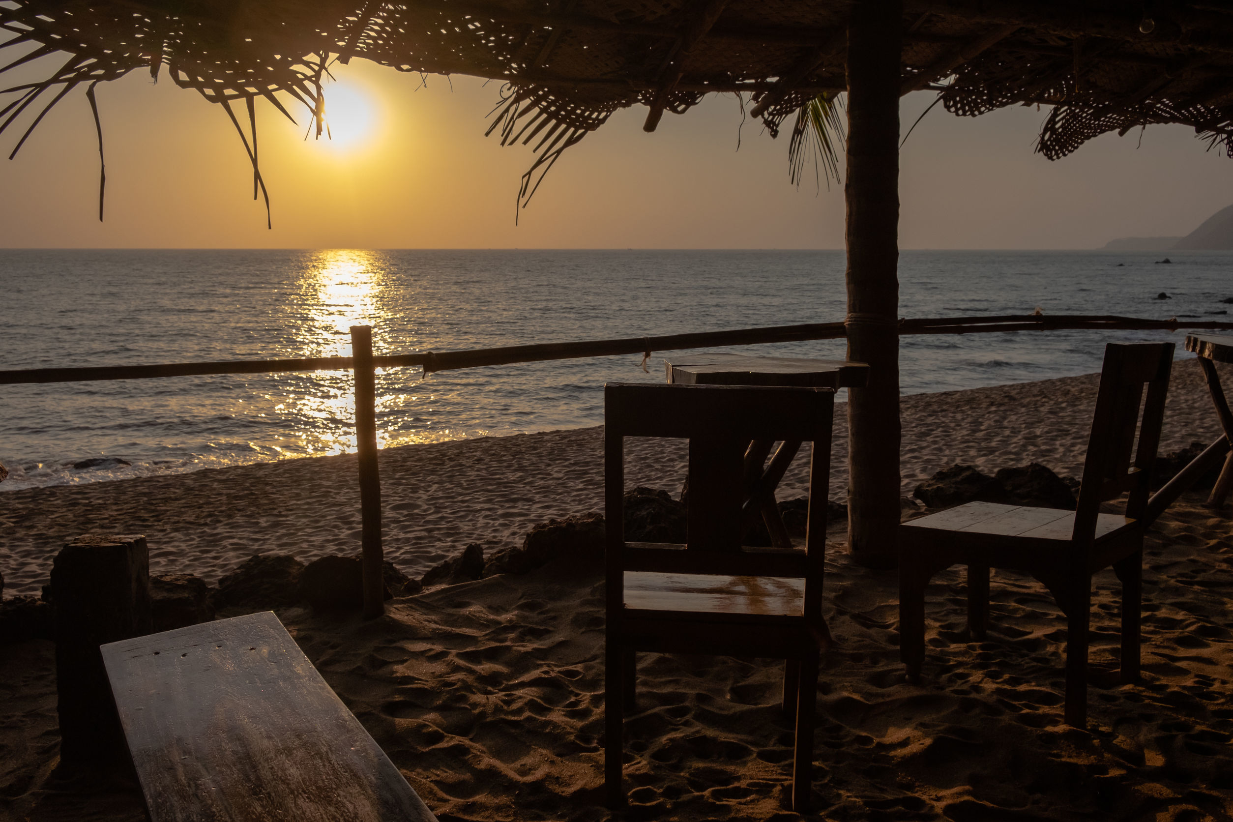 An empty wooden bar on the beach at sunset