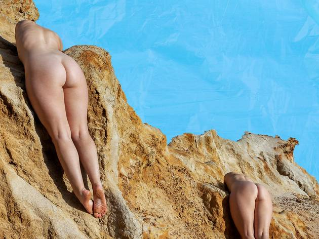 A couple of butts on a sandy cliff with a blue sky