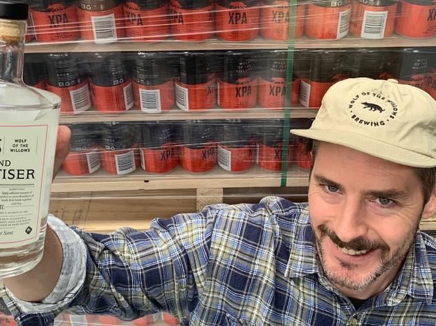 A man wearing a flannel shirt holds a glass bottle of hand sanitiser