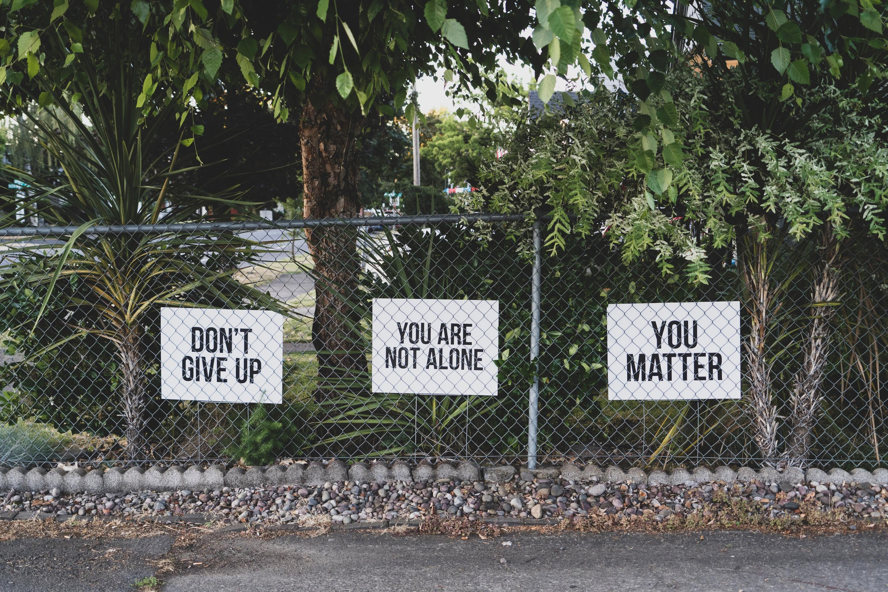 Signs on fences: Don't Give Up, You're Not Alone, You Matter