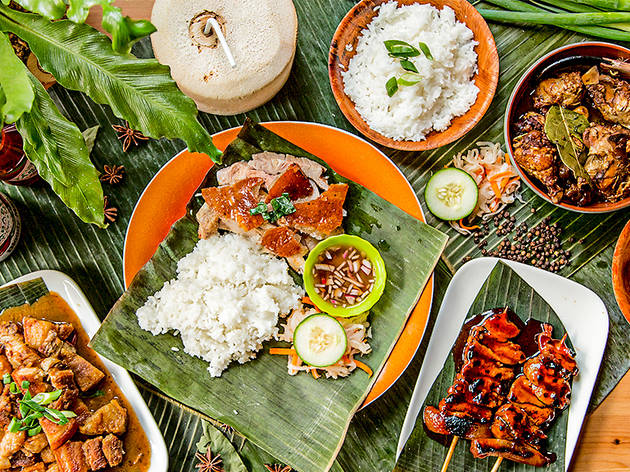 An overhead shot of roasted pork, skewers and rice laid out on banana leaves at Sydney Cebu Lechon