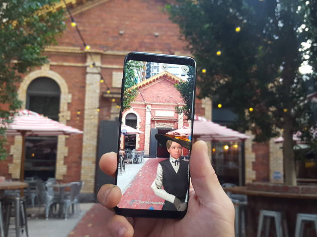 A mobile phone held up in front of a building reveals an augmented reality character.