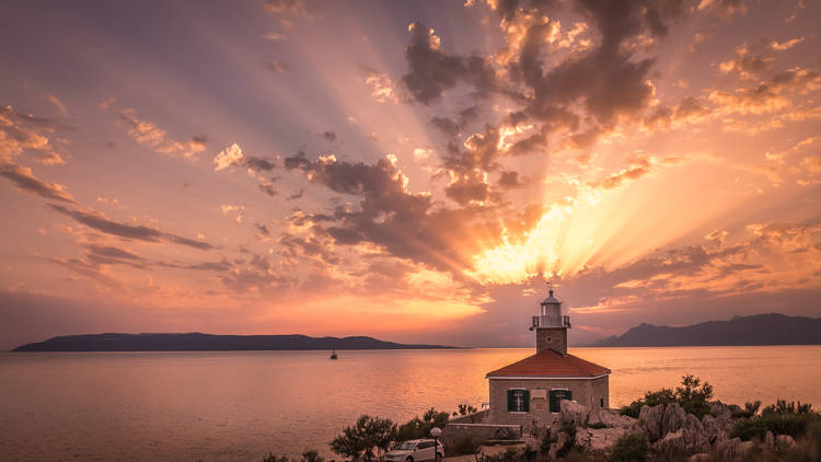 Sunset over Adriatic sea with lighthouse in the foreground in Makarska
