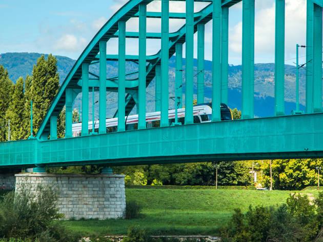 New modern fast train crossing green Railway bridge over Sava river in Zagreb