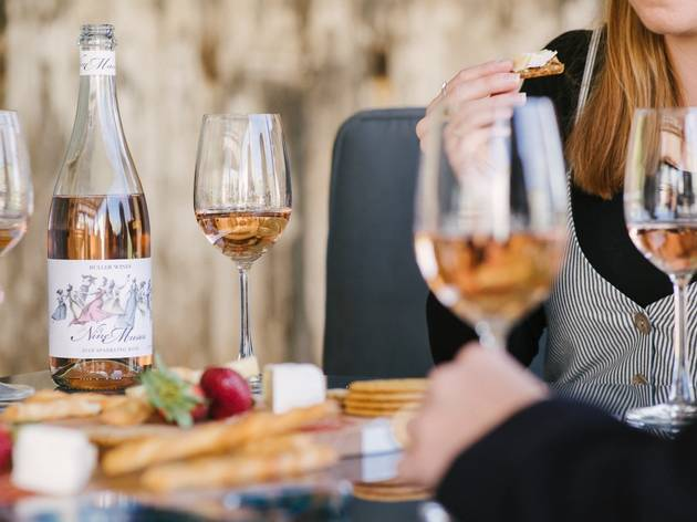 People sit around a table with glasses of rose wine and a cheese platter.