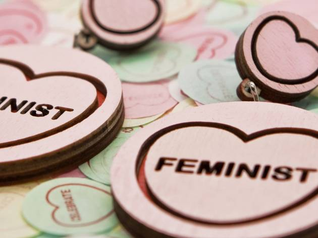 Round earrings with love hearts and 'feminist' laser cut into them