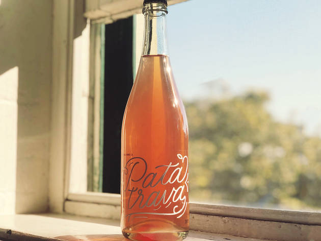 A bottle of wine from Ari's resting on a window sill in the sunshine.