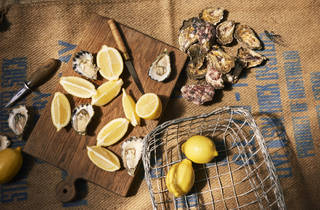 A combination of shucked and unshucked oysters on a chopping board with lemons.