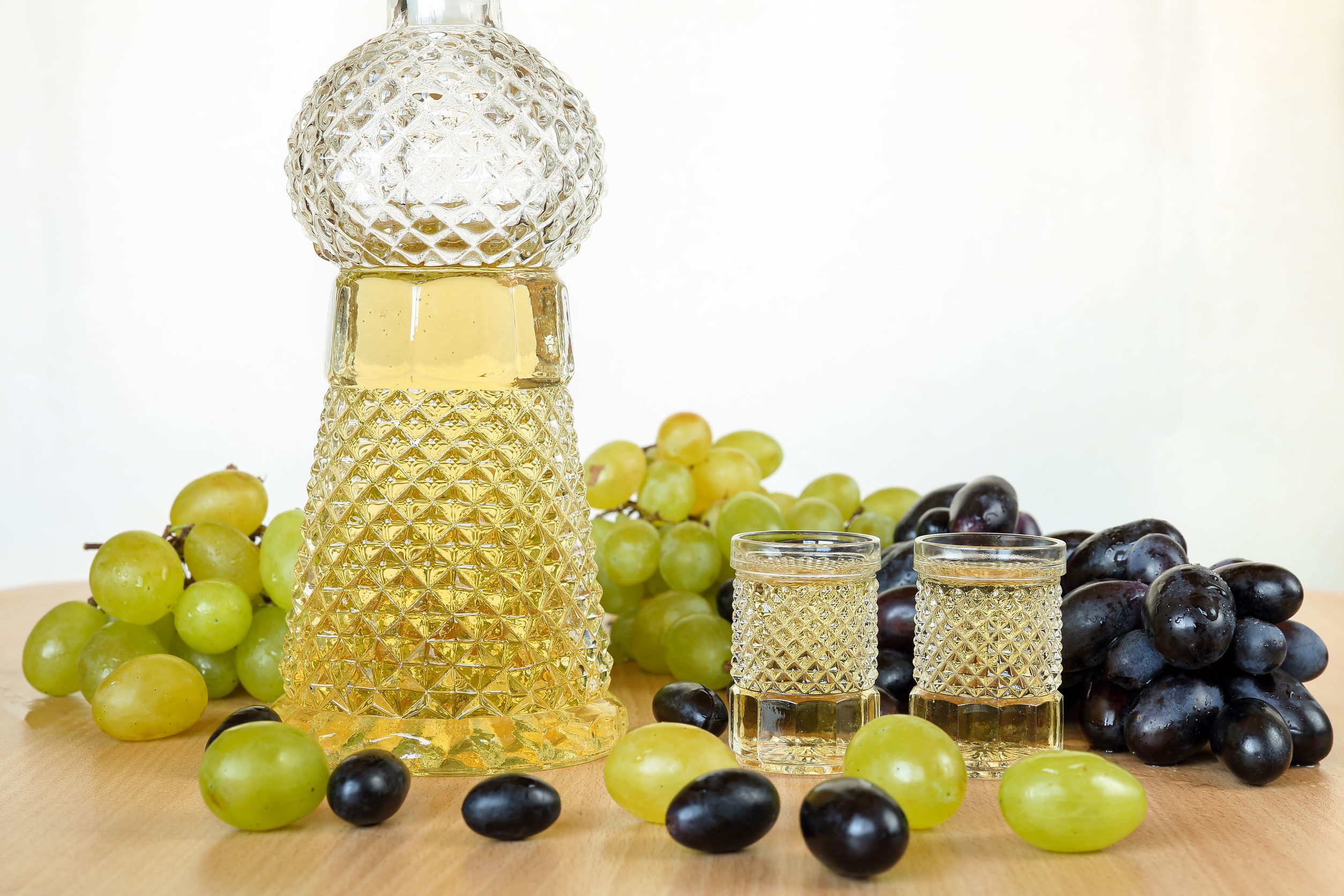 Traditional home made brandy tape fruit drink, called grozdova (grape) rakia, in crystal bottle and two glasses on a wooden table, white and black grapes around