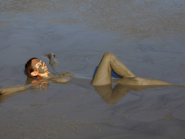 Girl takes useful procedures in the active mud volcano