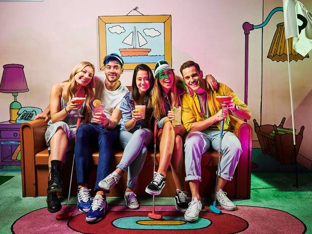 People sitting on a couch in a room styled to look like the living room in The Simpsons tv show