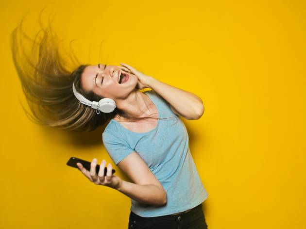 woman singing wearing headphones and holding phone