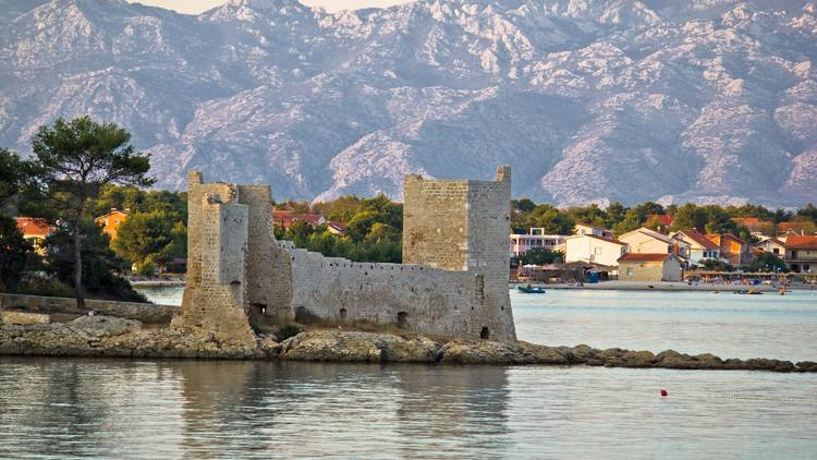 Island of Vir fortress ruins with Velebit mountain in background, Dalmatia