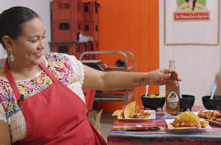 Rosa Cienfuegos holds a Jarritos soda next to a table of Mexican food