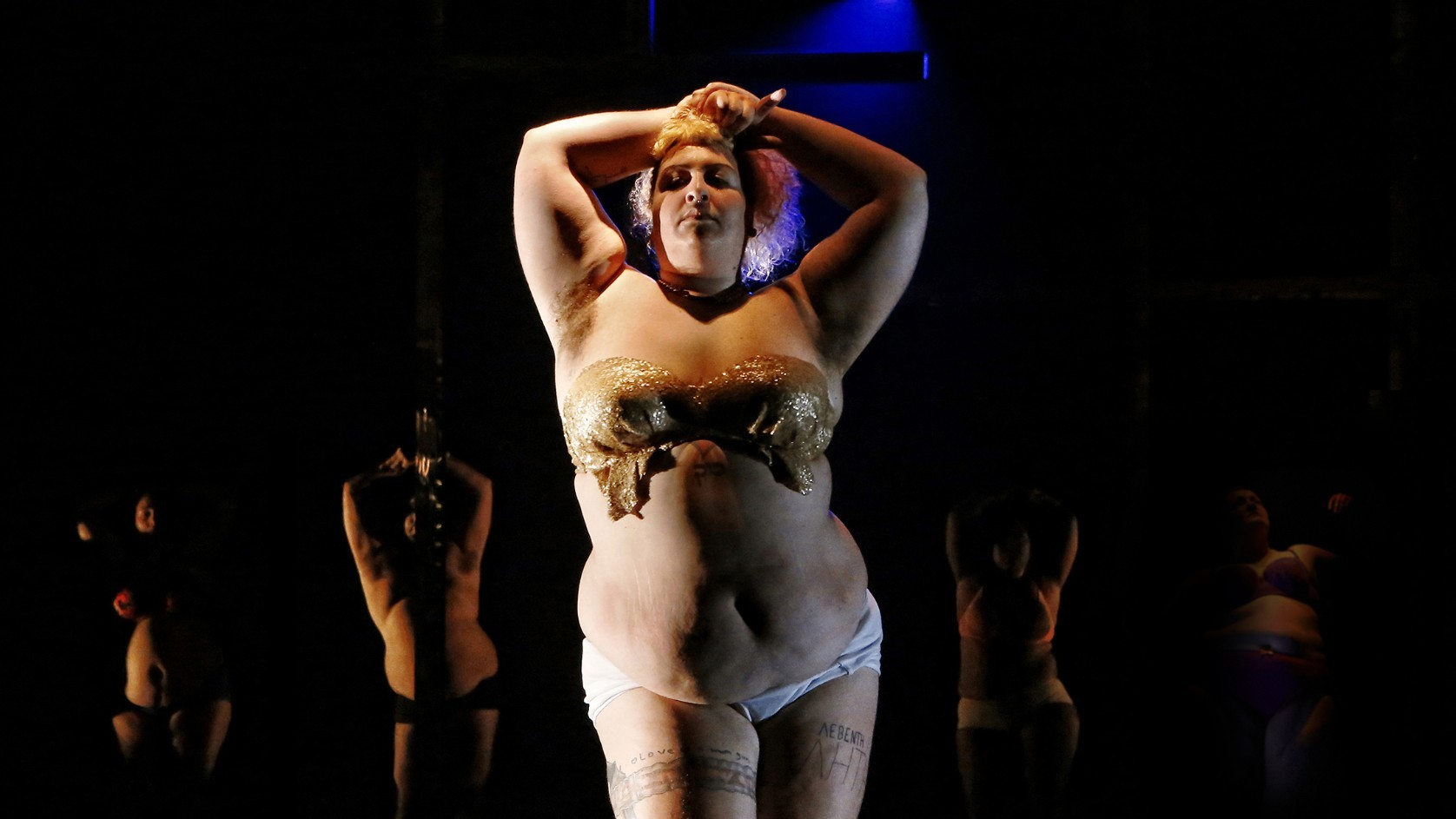 A performer wearing white underwear and a gold decorated strapless bra looks defiantly at the camera, their arms raised above their head.
