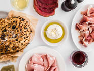 An overhead shot of puffy wood-fired bread and salumi on a table with wine and burrata.