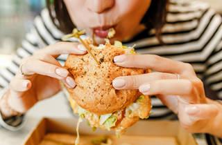 mujr comiendo hamburguesa