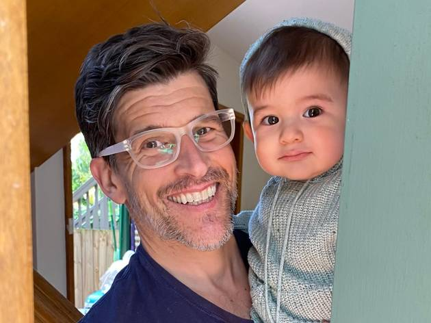 Osher opens the door, smiling, he is holding his infant son.