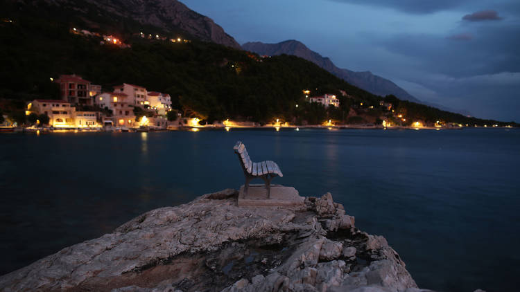Bench on large rock in sea on blurred luminous lights coastline with houses at foot of mountains background at evening.