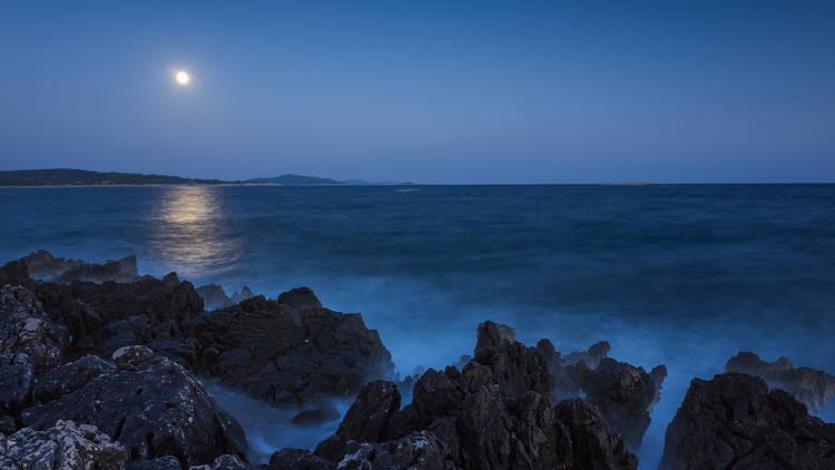 A craggy beach bear Šibenik soaks in the moonlight