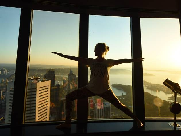 A yoga instructor holds a peaceful warrior pose, silhouetted against the Sydney skyline.