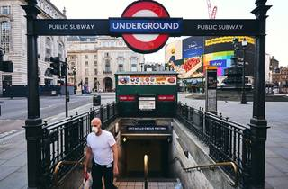man with face mask on london underground during lockdown