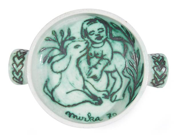 A white serving dish with a green animal and woman drawn on it by artist Mirka Mora