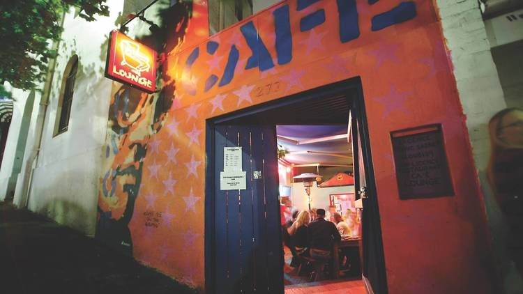 The doorway of Cafe Lounge, a painted blue wooden door opens with a neon sign overhead.