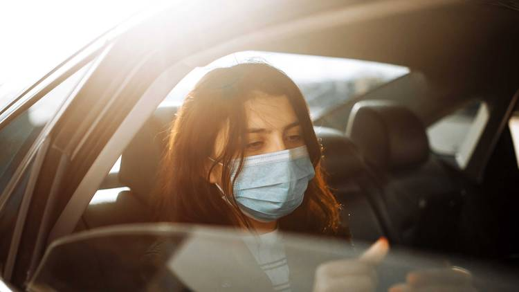 Person in back seat wearing mask