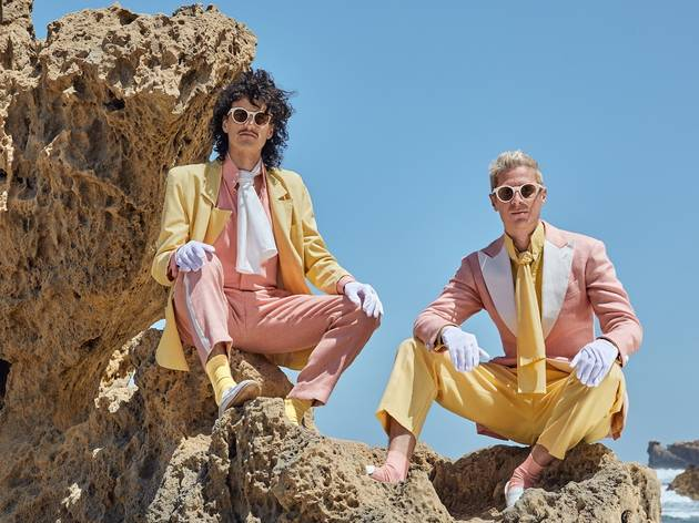 Two men in pink and yellow pastel suits pose on a rocky beach.