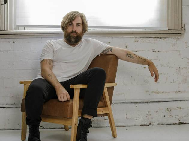 Josh Pyke sits in a chair in an edgy warehouse