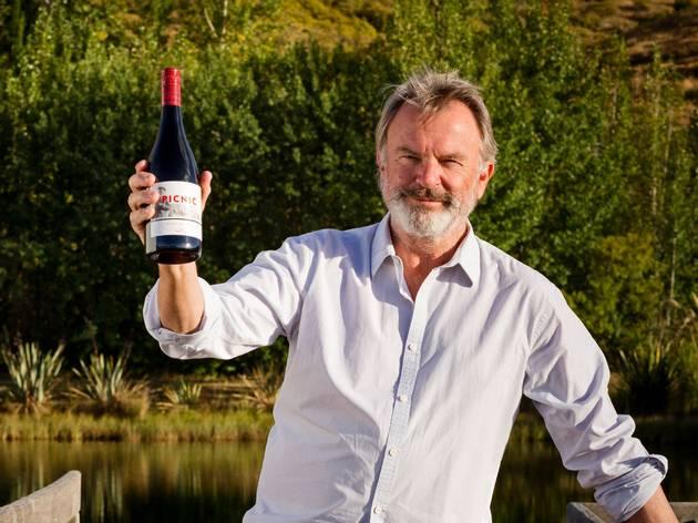 Sam Neill holding bottle of wine
