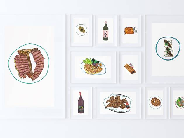 A white wall with an arrangement of framed food illustrations.
