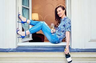 Woman sitting on windowsill holding Champagne