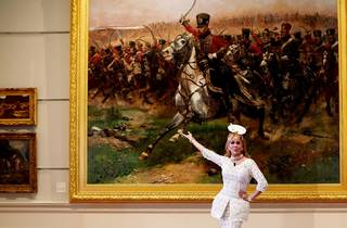 A Drag queen poses in front of a large painting depicting an army on horseback.