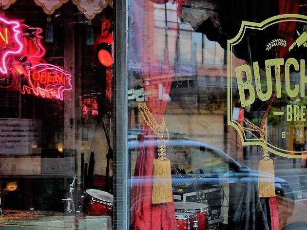 Shop window of a live music bar reveal red curtains, drums and a neon 'open' sign.