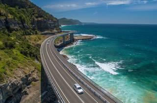 Car driving over bridge aerial view