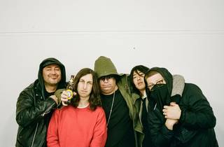 Band poses, huddled together in front of a blank wall. one holds a beer.