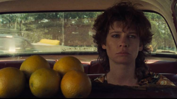 Woman frowning in the back of a car with oranges