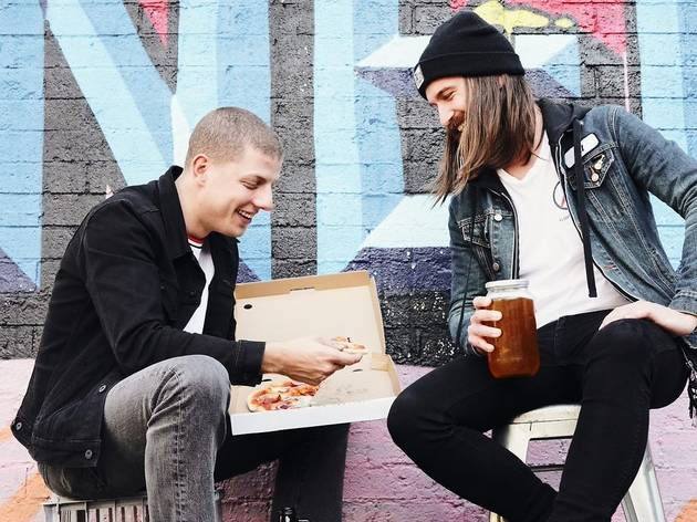Two guys sit outside, one holds a pizza and another holds a jar of beer.
