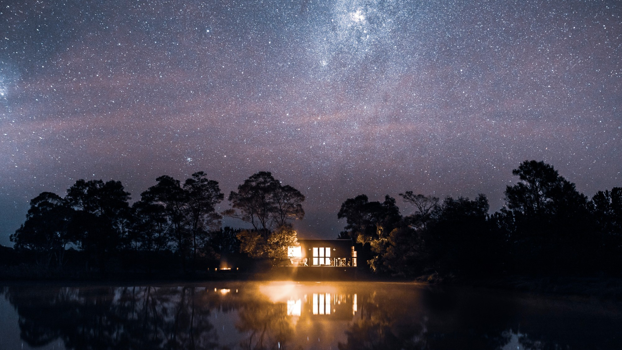 A tiny cabin is illuminated against a night sky.