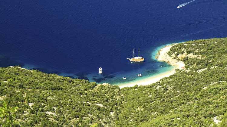 View on Lubenice Beach with tourist pirate ship and few boats at dark blue sea, surrounded by Mediterranean trees. Cres, Croatia.
