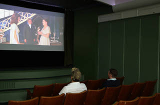 Two people sit in a small theatre watching a movie