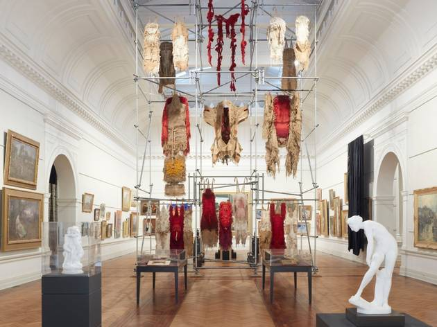 An installation of traditional garments hanging from scaffolding in a gallery.